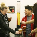 Friends using beer tower at a party